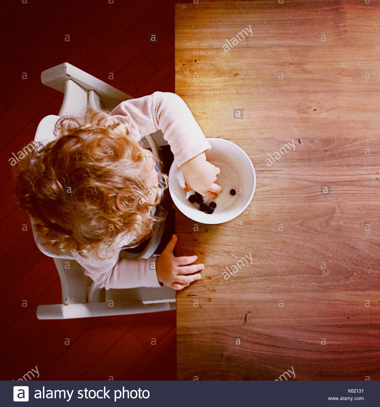 Overhead view of girl (2-3) eating blueberries - Stock Image