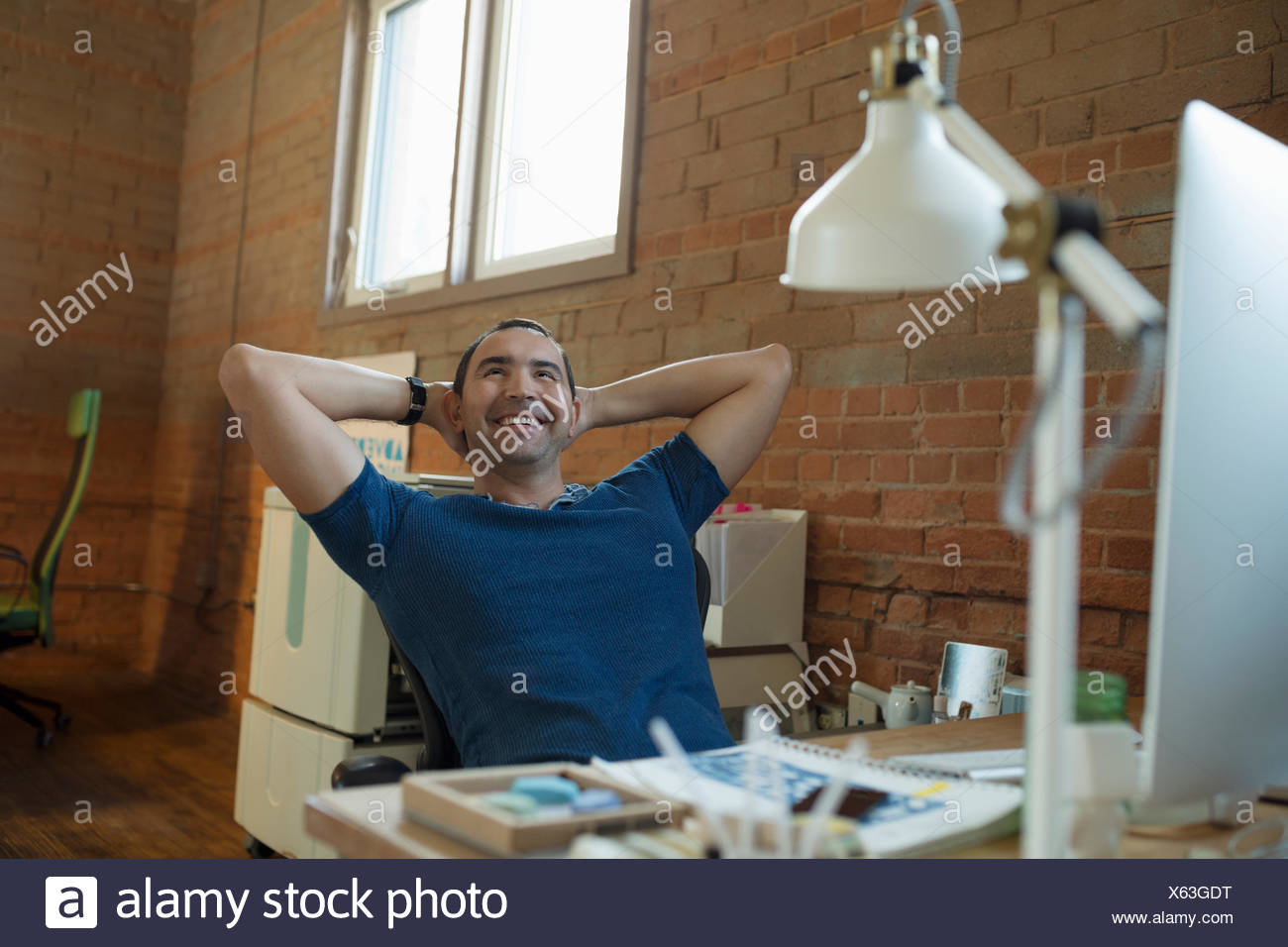 Happy creative businessman sitting at desk with hands behind head - Stock Image