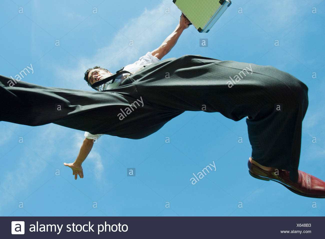 Businessman jumping in air carrying briefcase, directly below - Stock Image