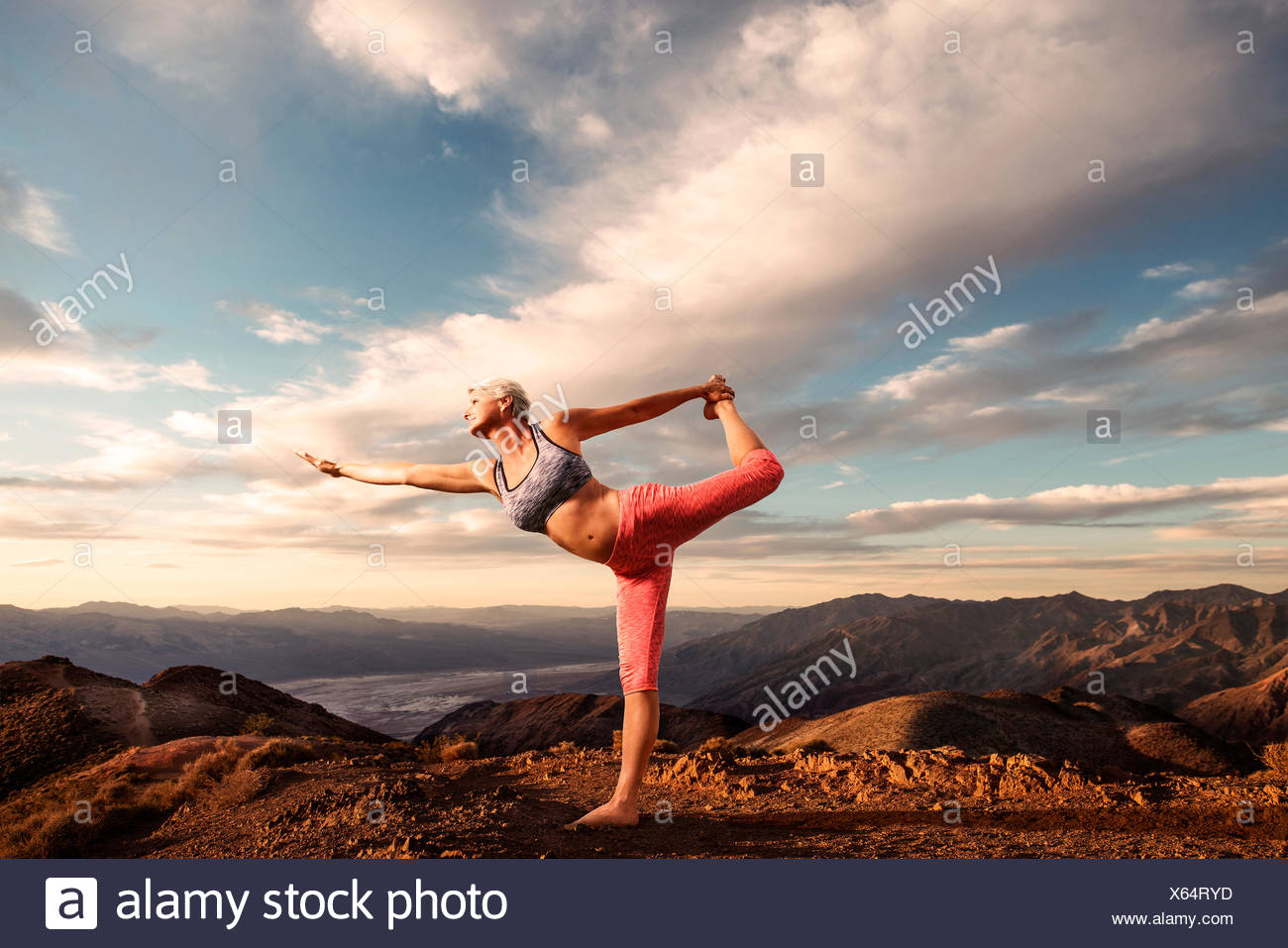 Senior woman doing yoga pose on top of mountain at sunset with landscape and desert valley below. - Stock Image