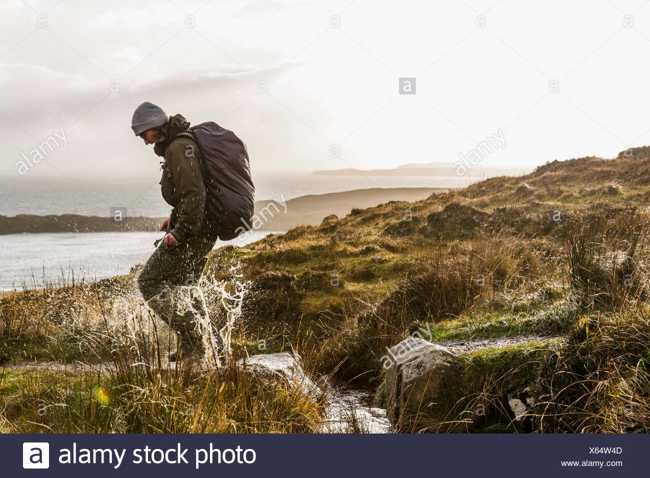 A man with a rucksack and winter clothing leaping across a small stream in an open exposed landscape. - Stock Image
