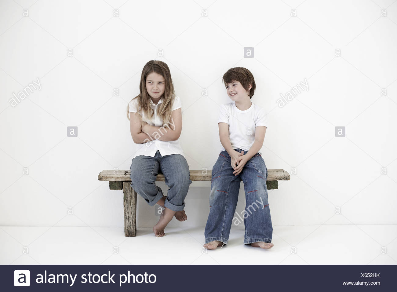 Young boy smiling at shy young girl - Stock Image