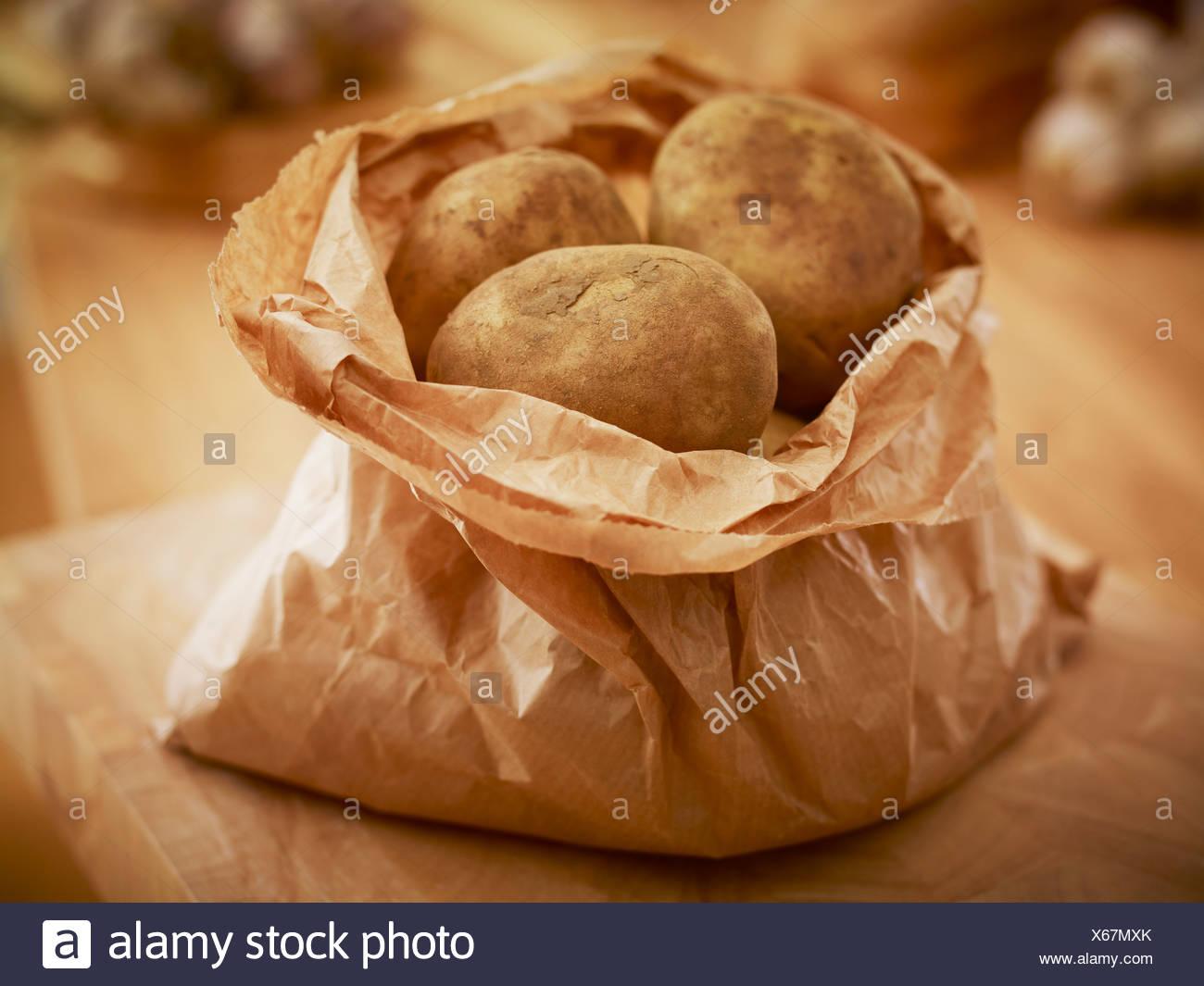 Organic potatoes in paper bag - Stock Image