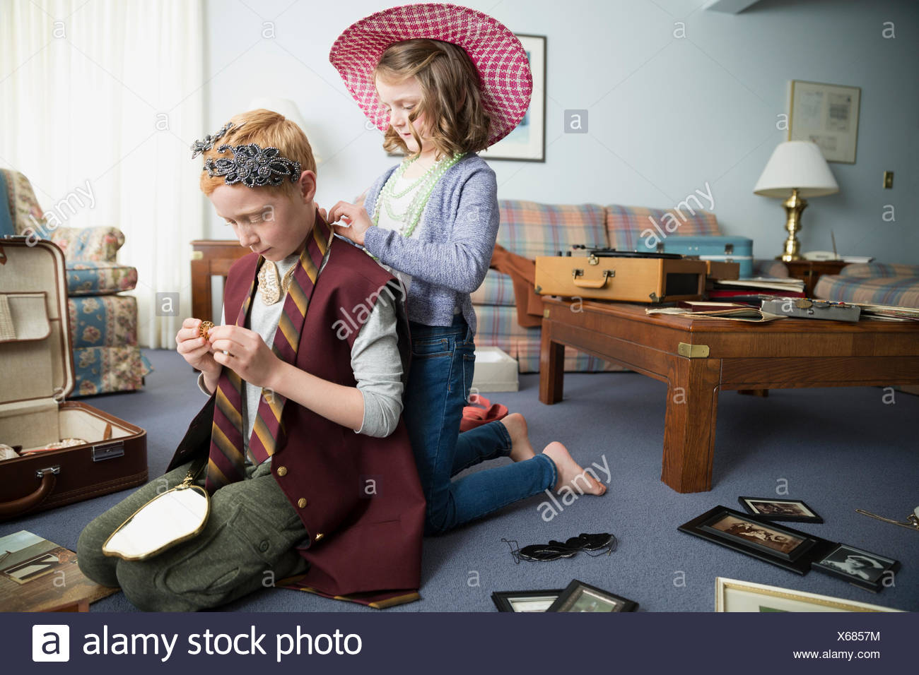 Brother and sister trying on old-fashioned clothing - Stock Image