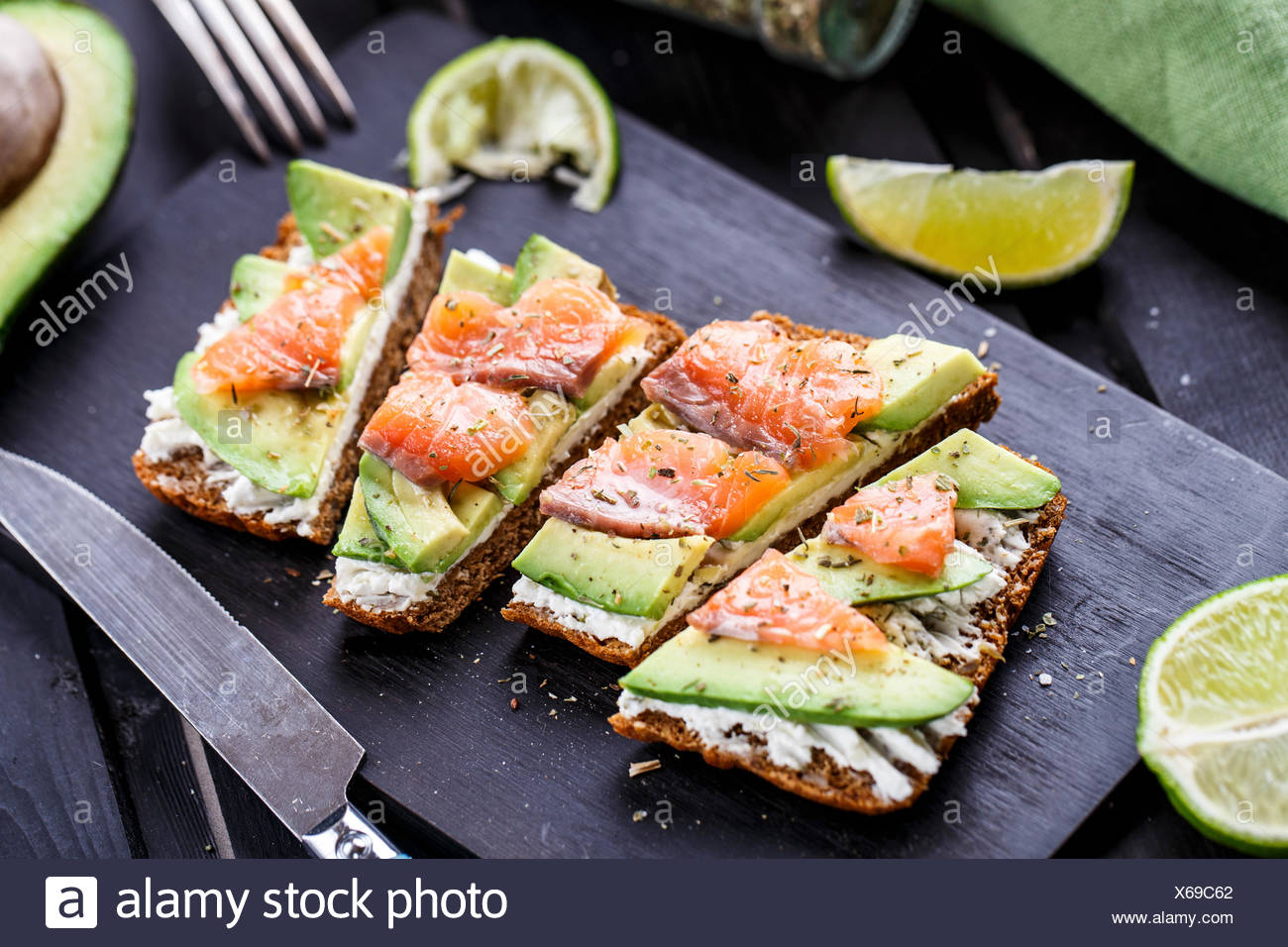 Sandwich with avocado and smoked salmon on a black wooden board - Stock Image