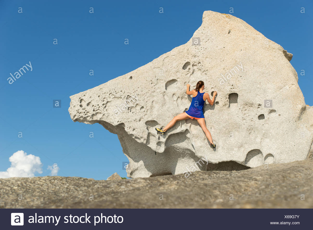 France, Corsica, Young woman climbing big rock - Stock Image