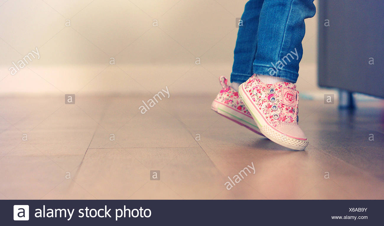 Baby girl learning to stand on her feet - Stock Image