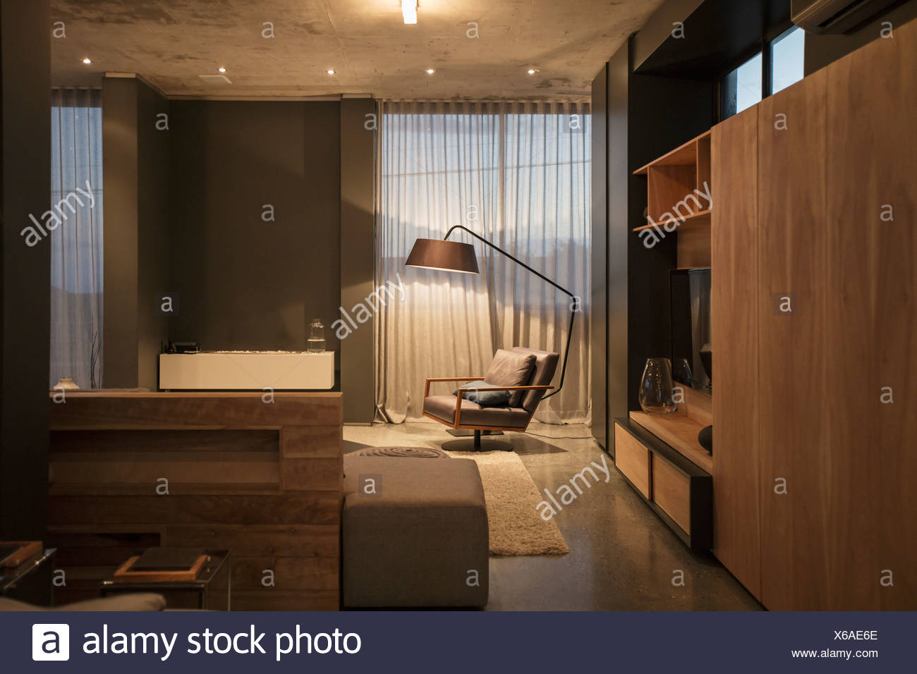 Chair and floor lamp in corner of modern living room - Stock Image