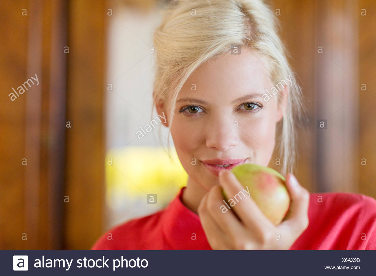 Woman eating apple indoors - Stock Image