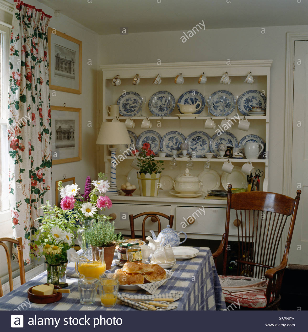 Blue White China Collection On Cream Dresser In Cottage Dining Room With Table Set For