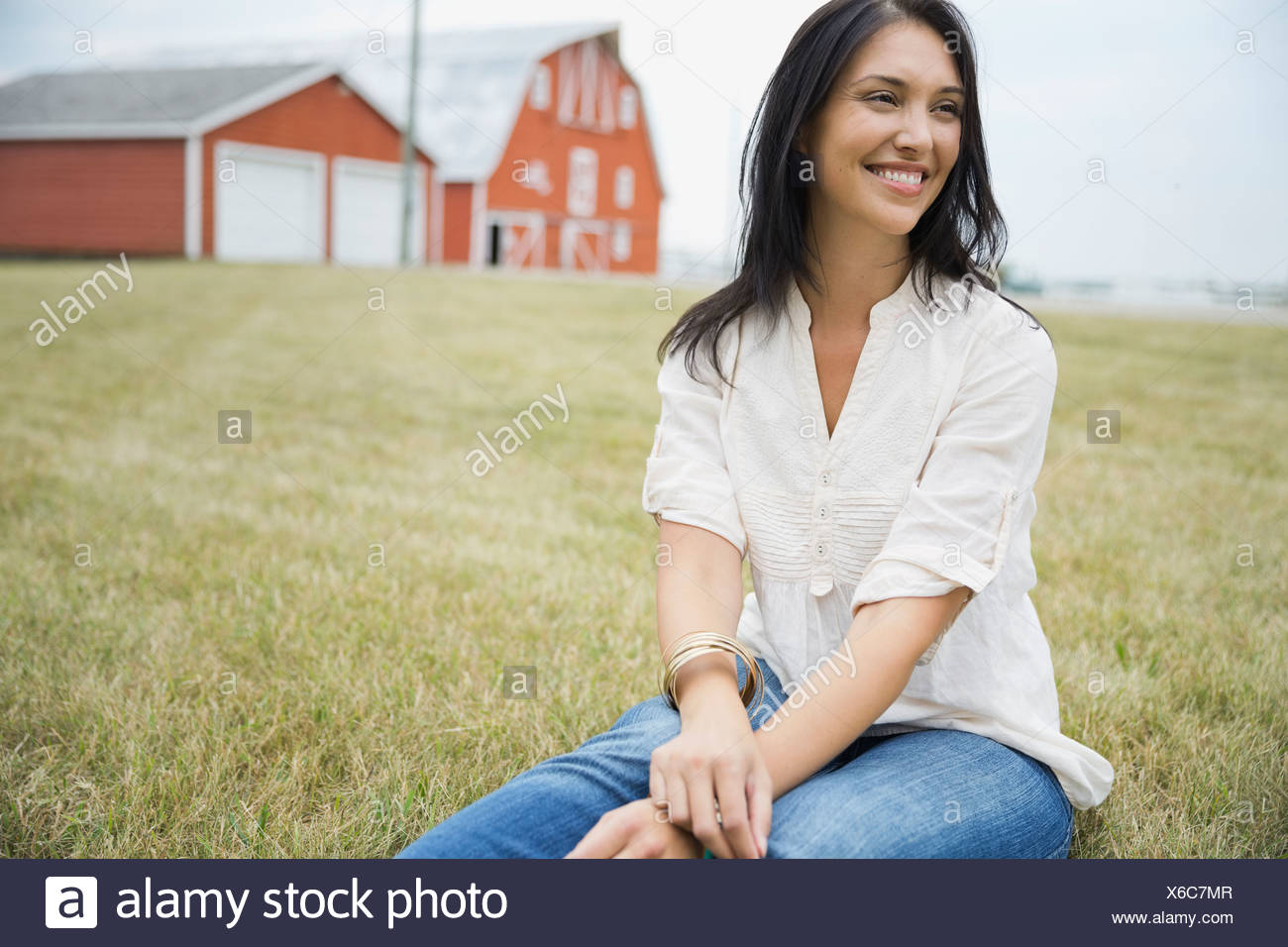 Smiling woman sitting outdoors - Stock Image