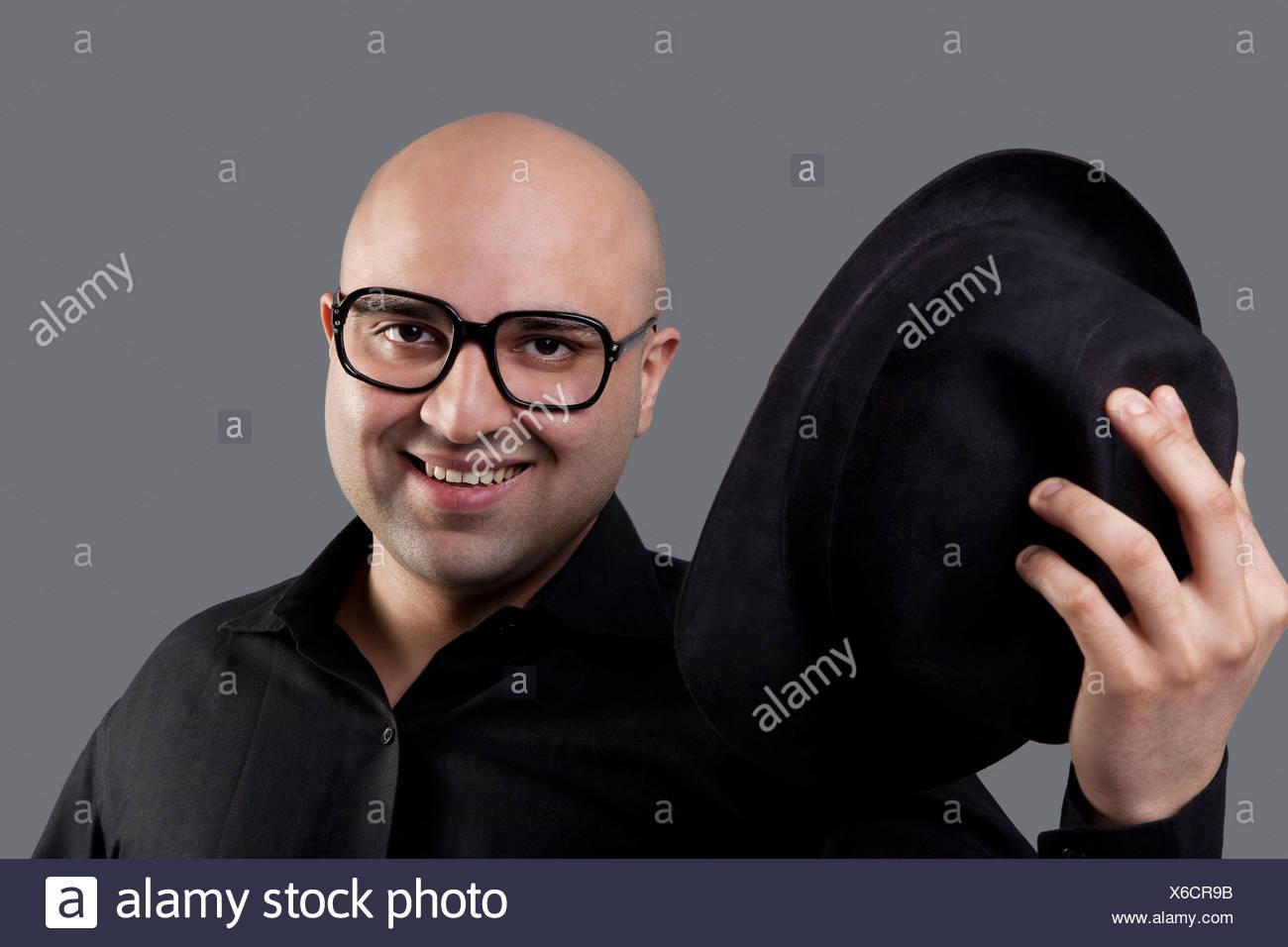 Bald man taking off his hat - Stock Image