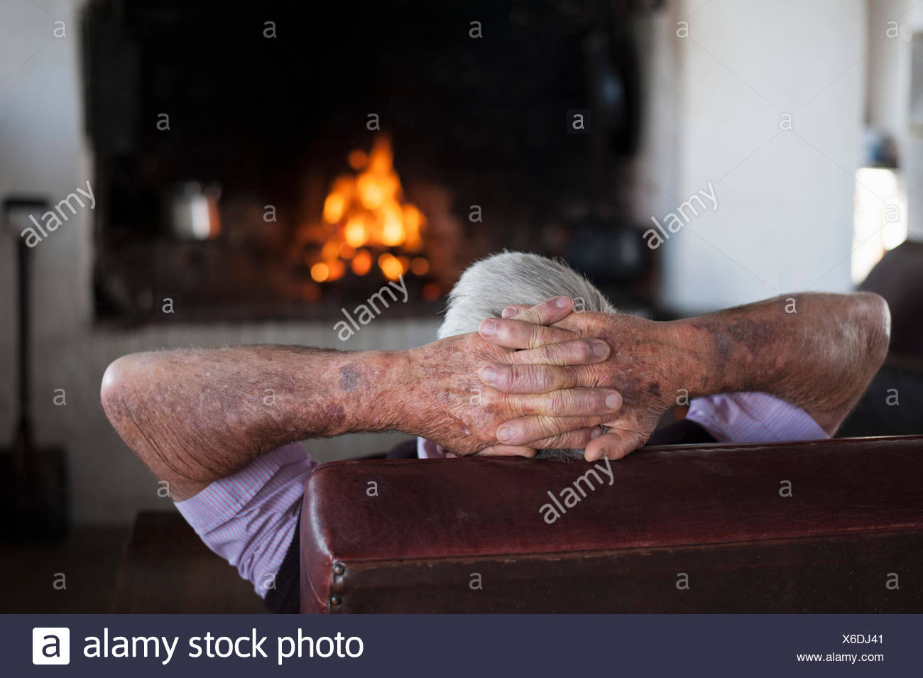 Rear view of senior man at home with hands behind his head in front of log fire - Stock Image