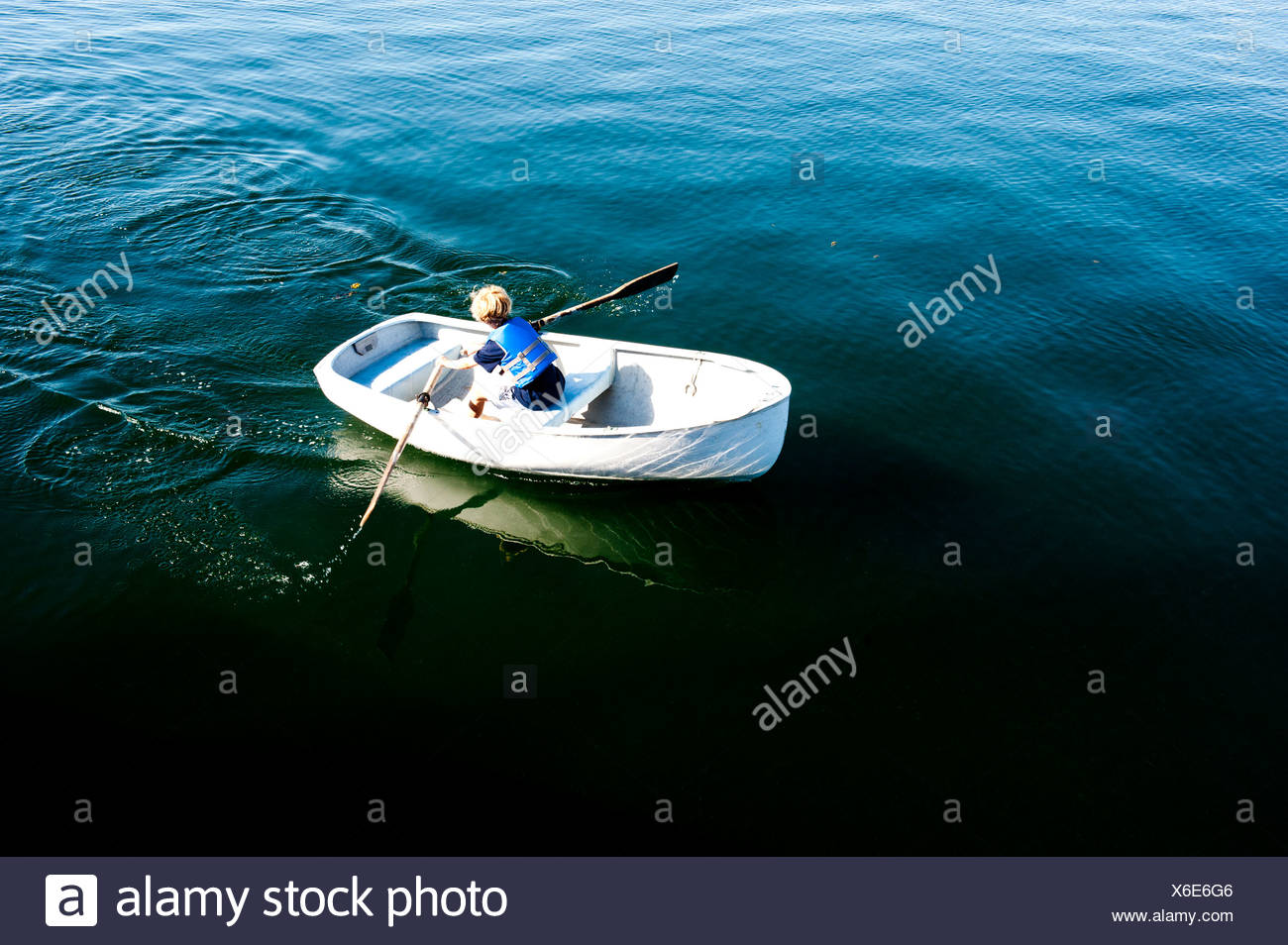a boy rows a boat off an island in maine - Stock Image