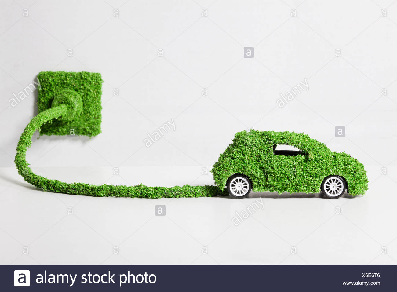 Electric car covered with grass connected to socket, close up - Stock Image