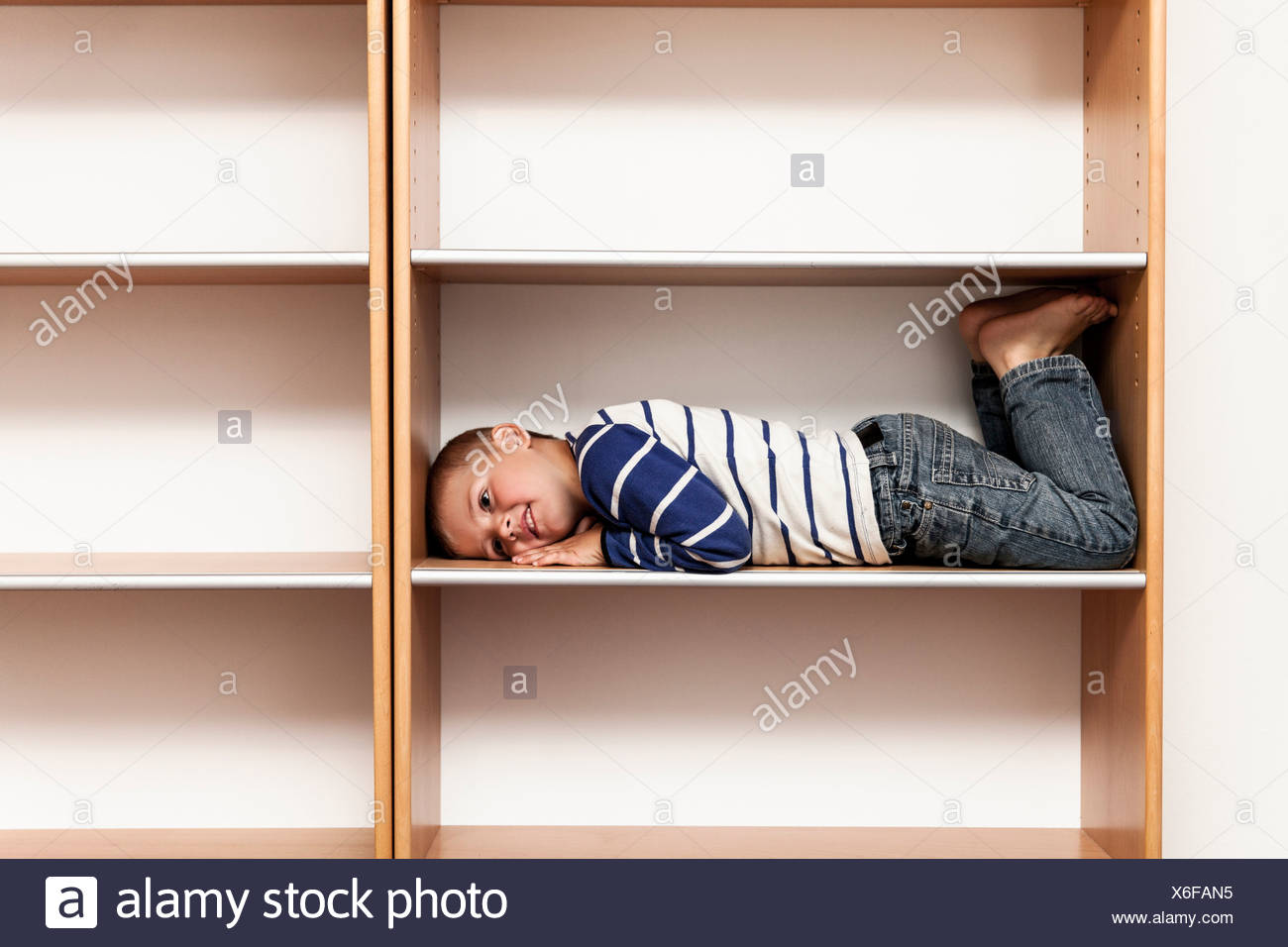 Full length of playful boy lying in empty shelf at home - Stock Image