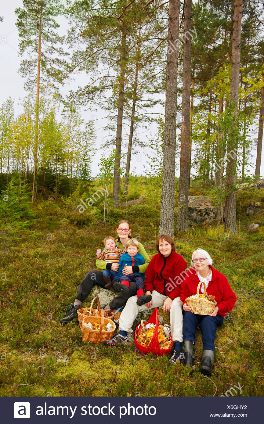 Family with mushroom baskets in forest - Stock Image
