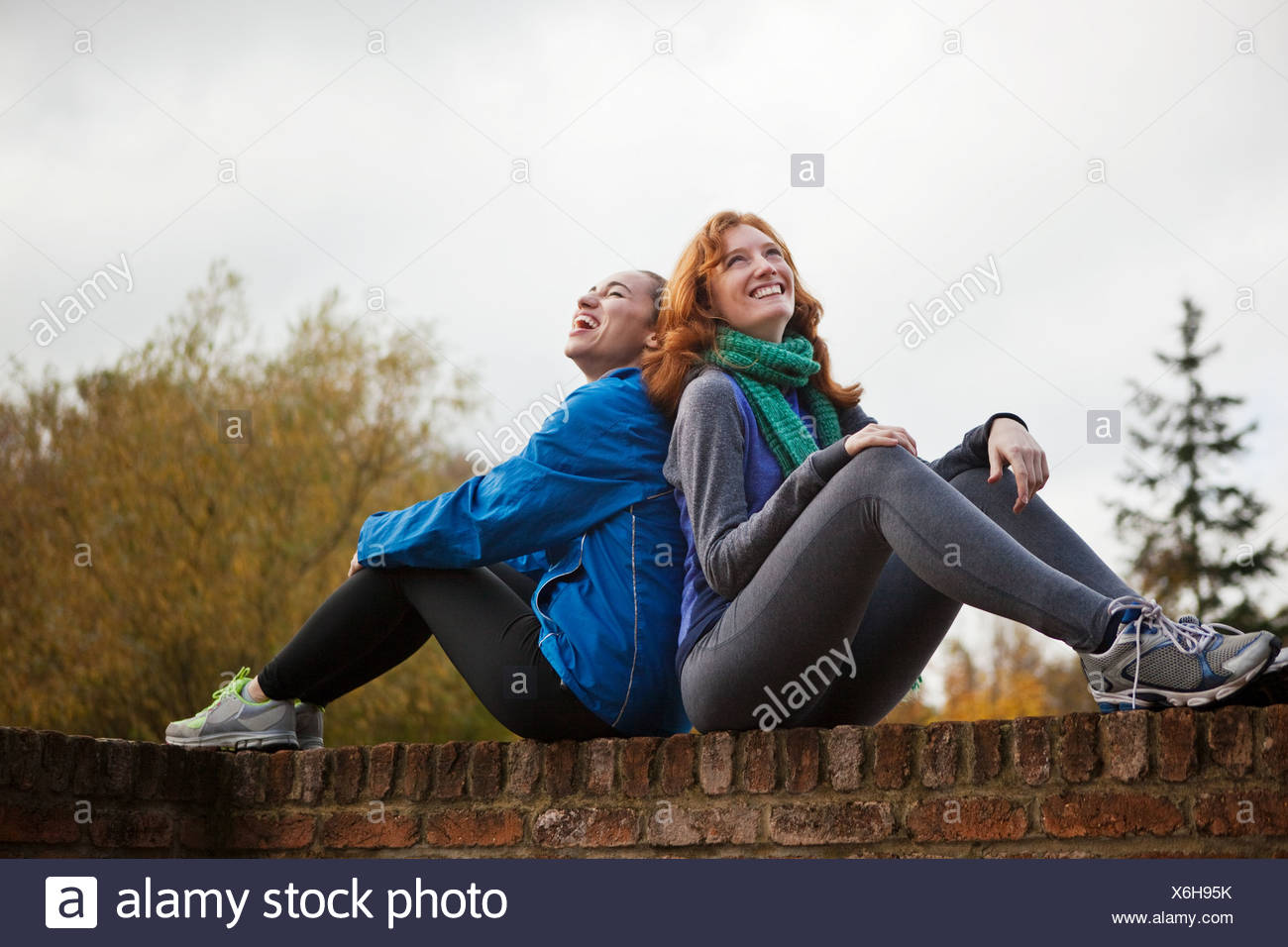 Young women sitting back to back on brick wall - Stock Image