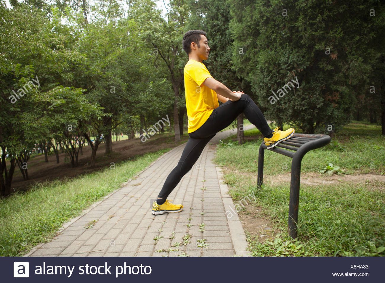 Young male runner warming up in park - Stock Image
