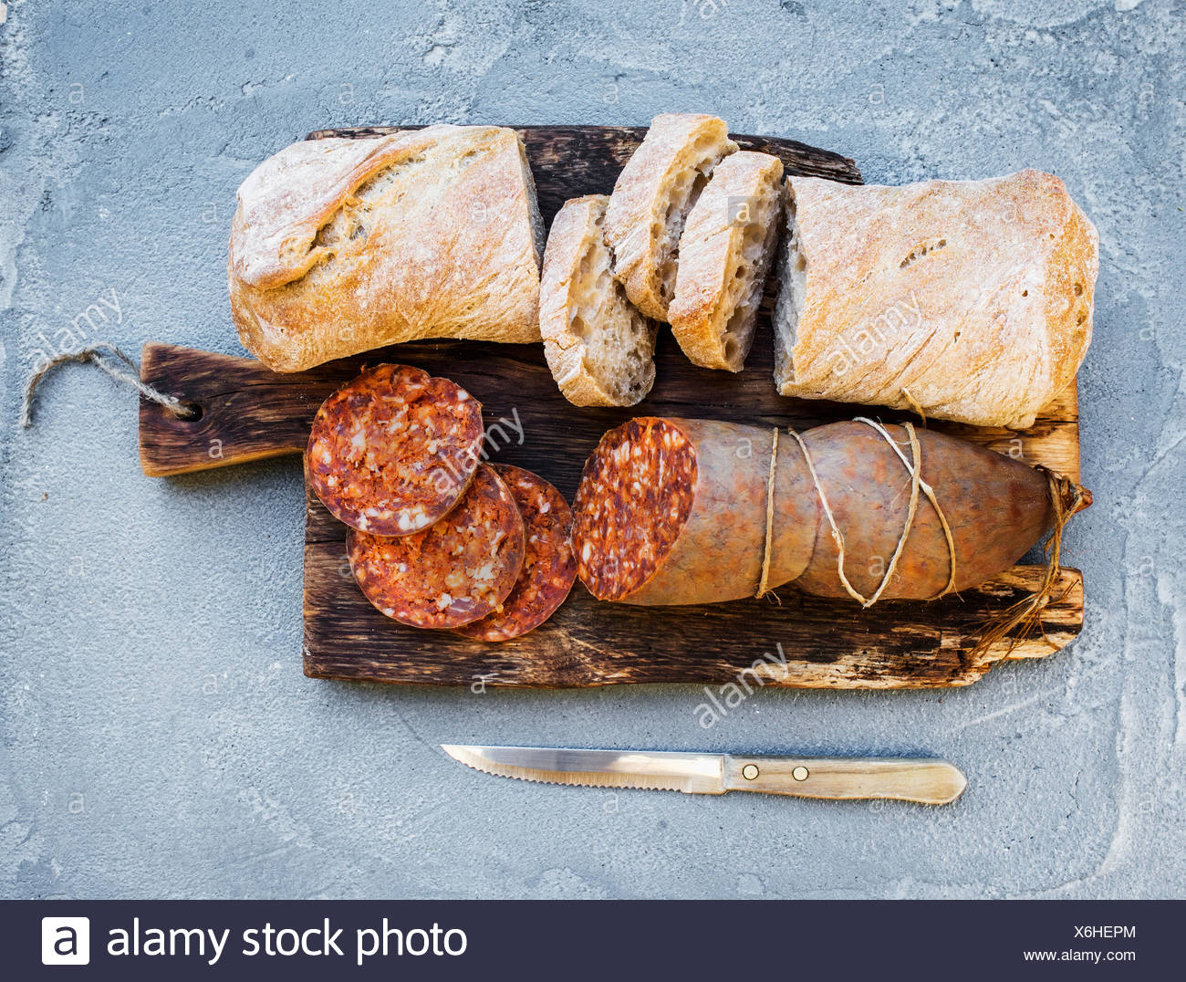 Wine snack set. Hungarian mangalica pork salami sausage and rustic bread on dark wooden board over a rough grey-blue concrete ba - Stock Image