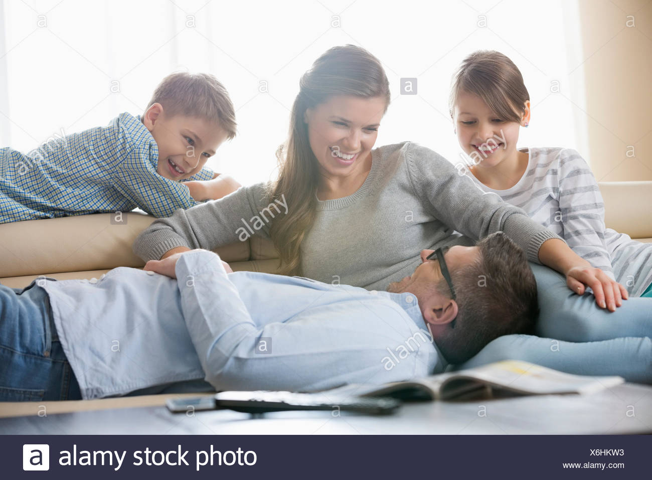 Happy family in living room - Stock Image