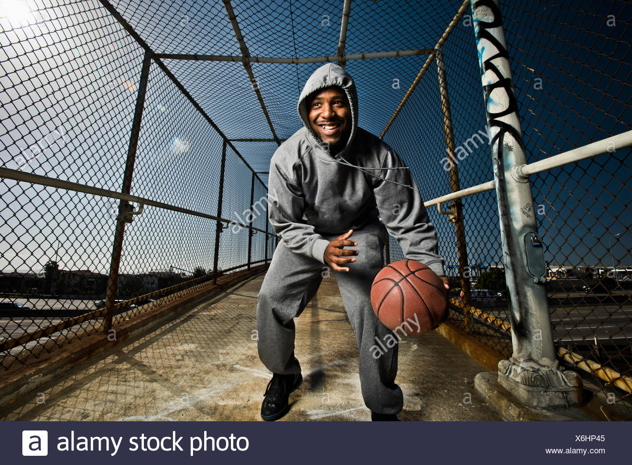 A young man playing around with a basketball. - Stock Image