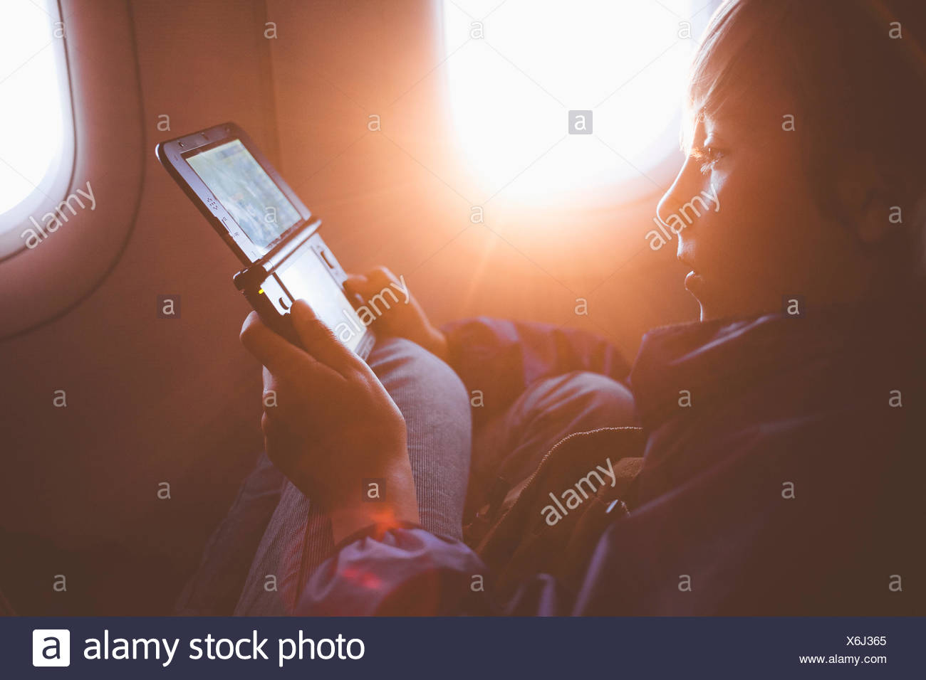 Boy playing with handheld video game - Stock Image