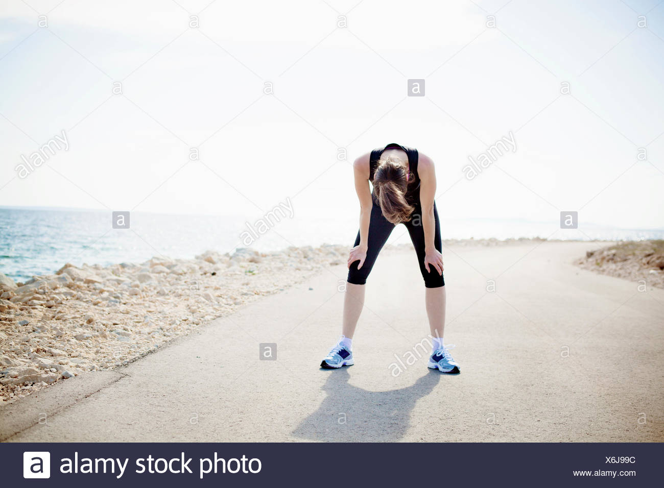 Woman in sports clothing standing on waterfront path - Stock Image