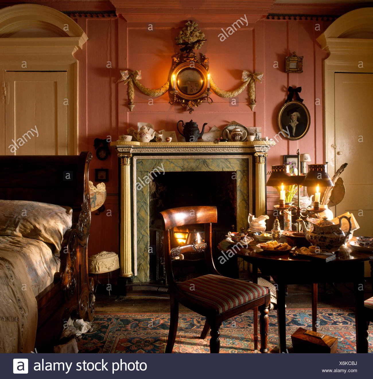 Antique Furniture In A Pink Georgian Bedroom With An Ornate Gilt Mirror  Above The Fireplace