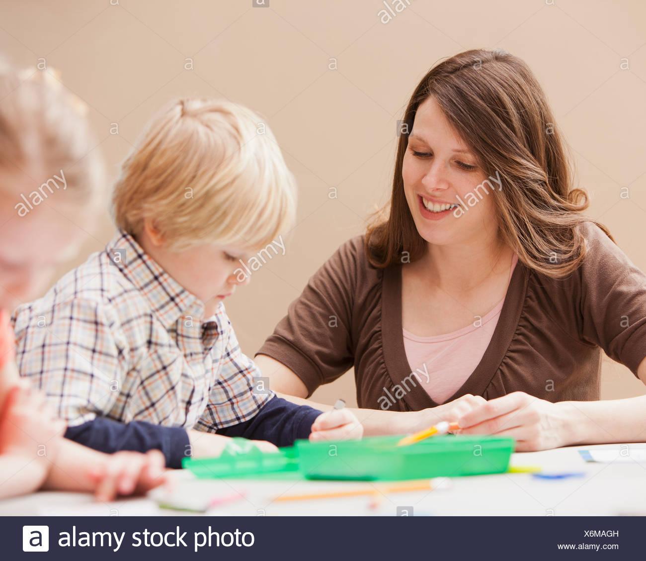 Mid adult woman teaching boy (4-5) drawing in kindergarten - Stock Image