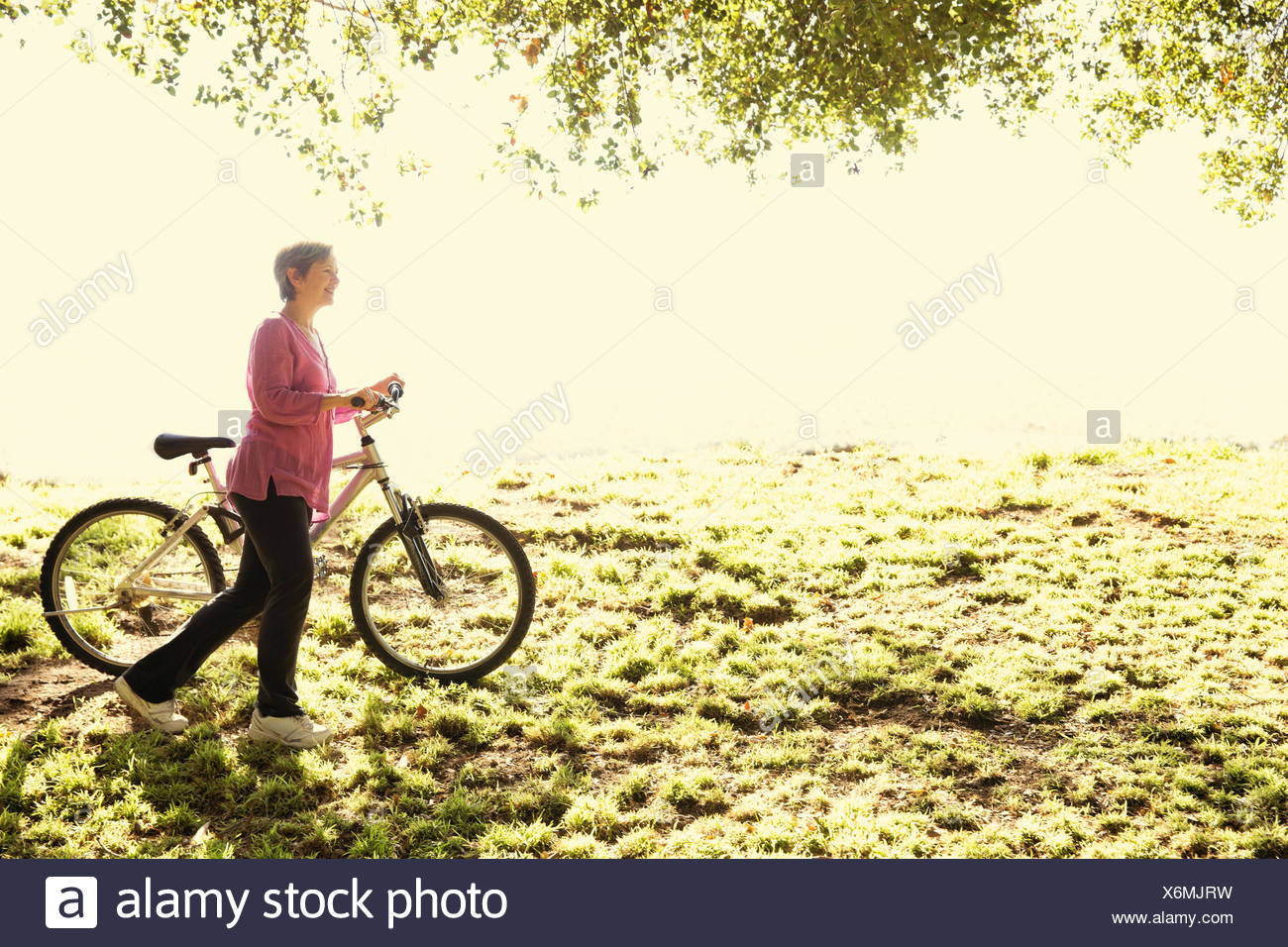 Mature woman pushing bicycle in park - Stock Image