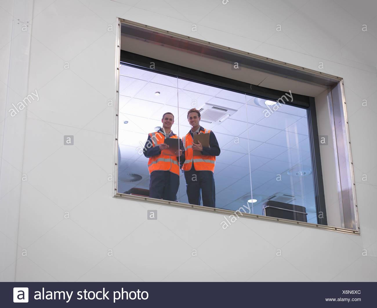 Engineers look out of window in hangar - Stock Image