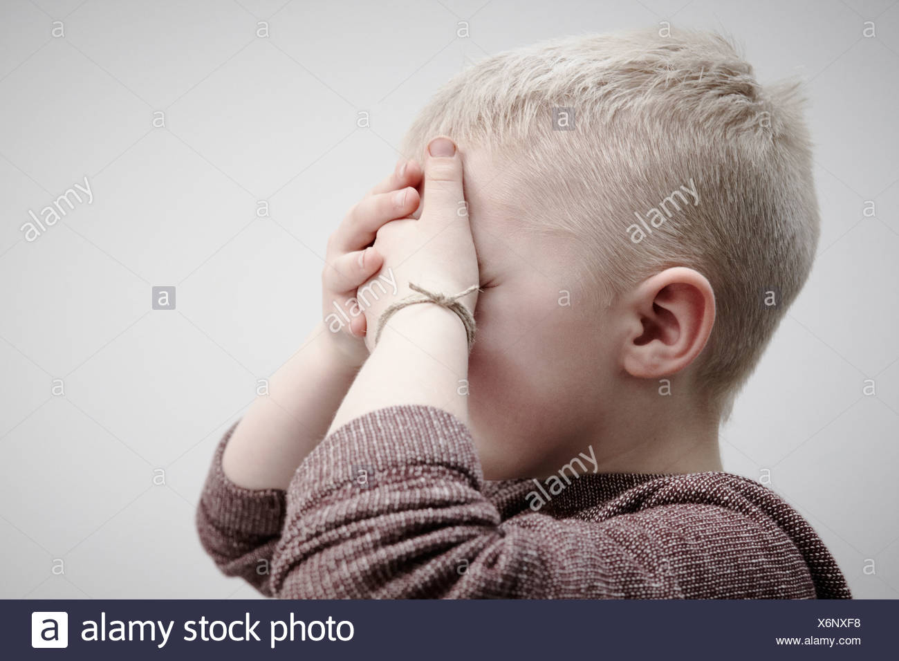 Portrait of boy wearing brown jumper, covering face with hands - Stock Image
