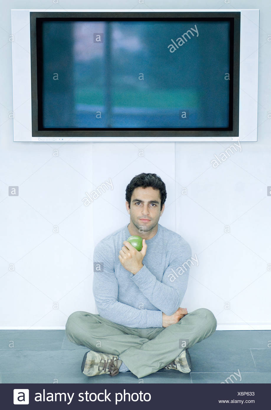 Man sitting on floor under wide screen TV, holding apple - Stock Image