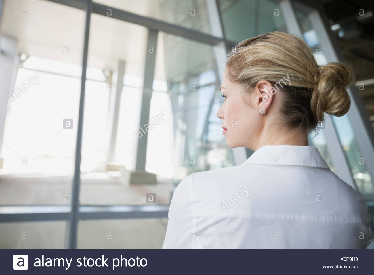 Rear view of pensive blonde businesswoman looking away - Stock Image