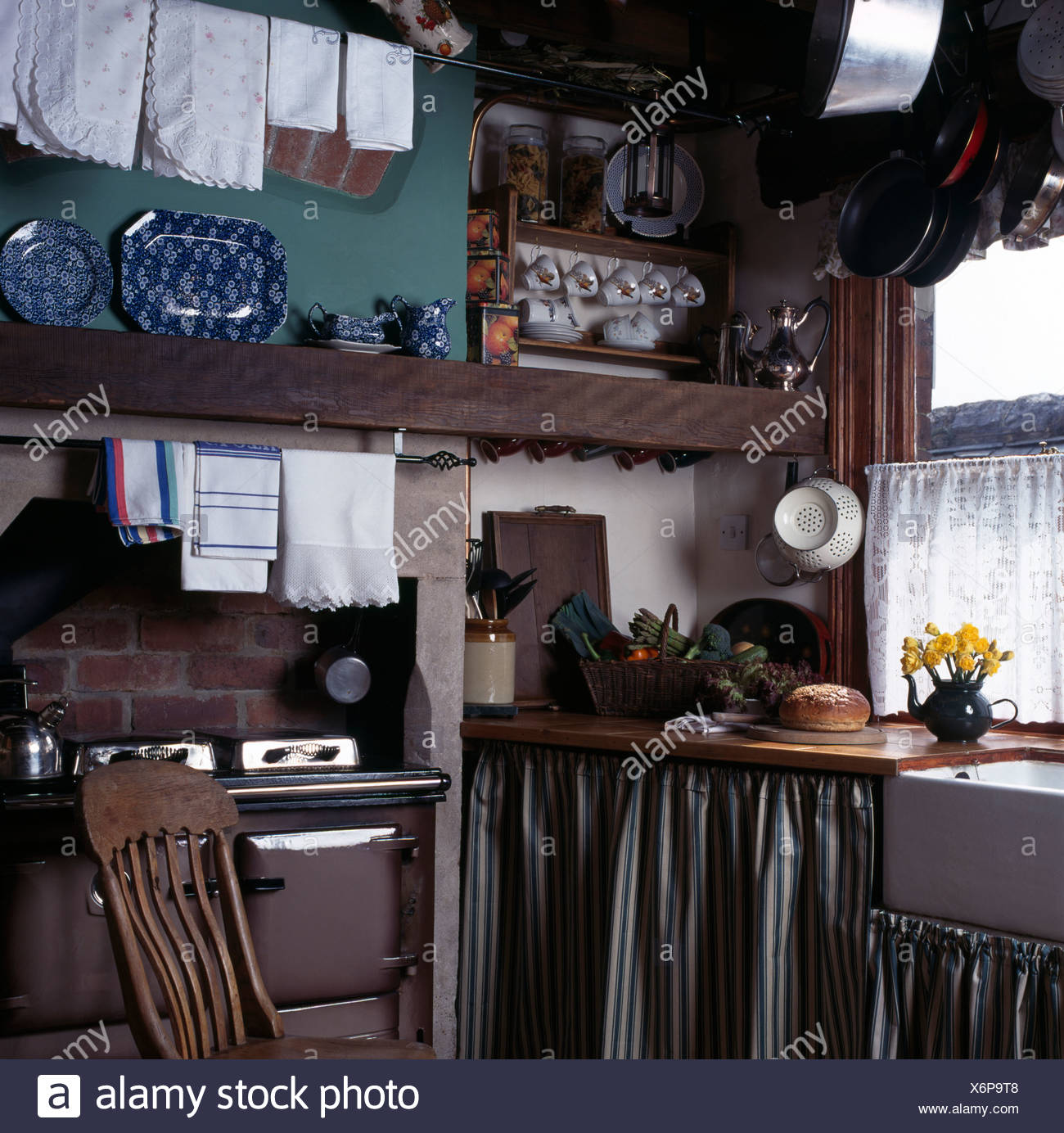 Striped curtains on units in small cottage kitchen with linen airing on rail above brown range oven