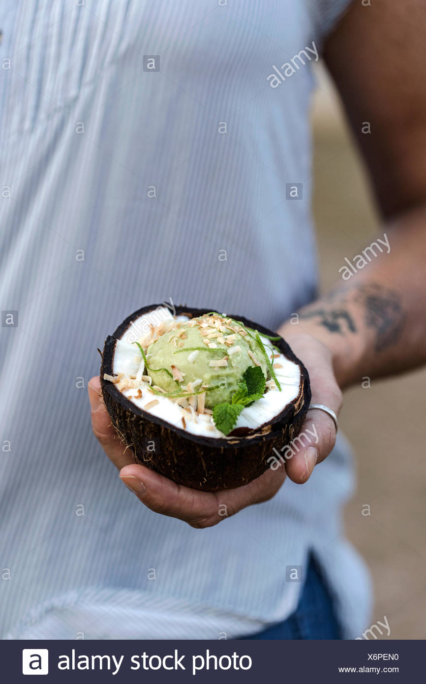 A woman is holding a coconut bowl filled with a scoop of coconut and avocado ice cream. - Stock Image