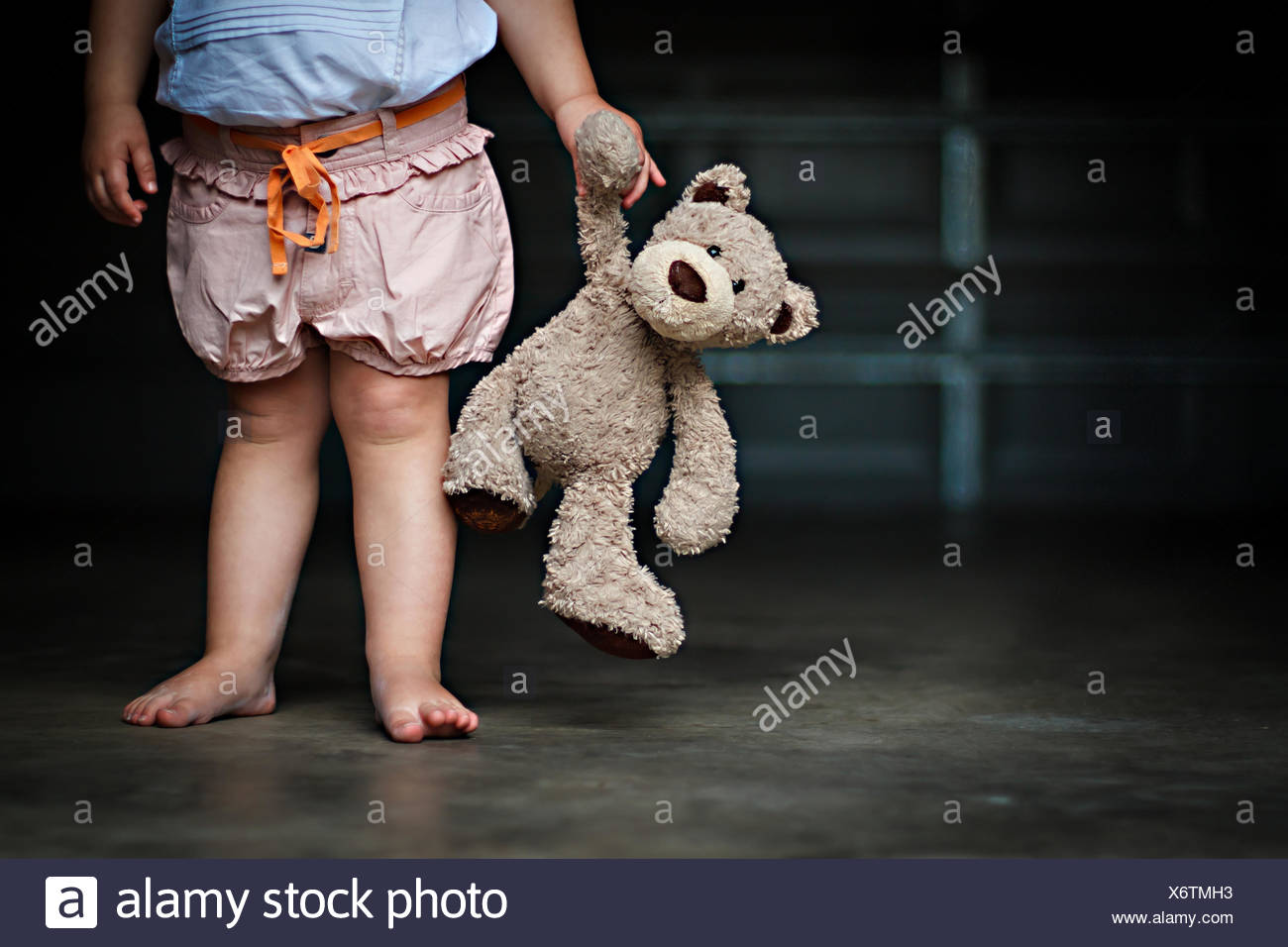 Low section of a girl holding her teddy bear - Stock Image