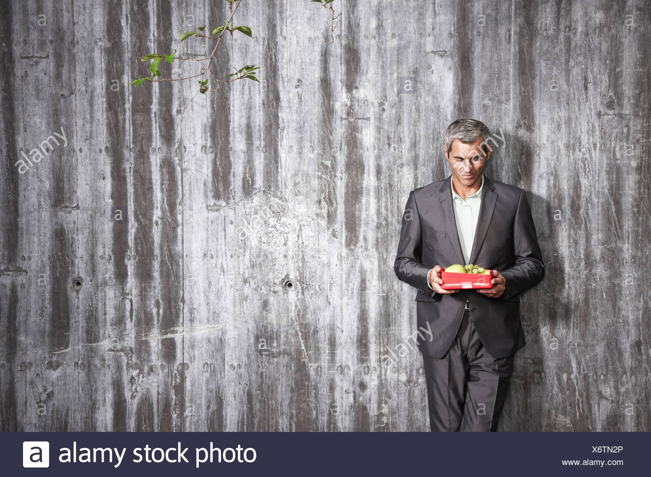 businessman holding box with fruits - Stock Image