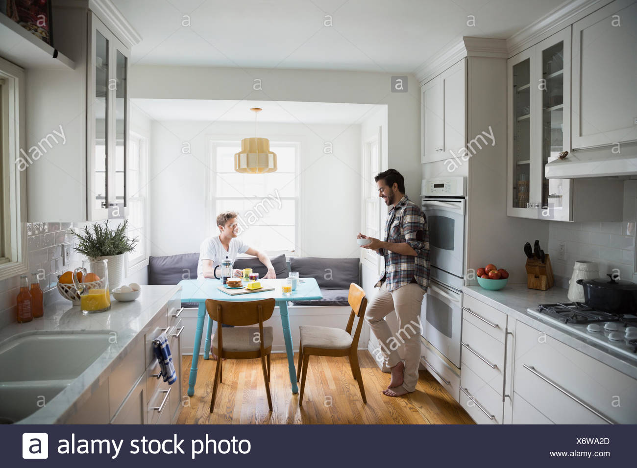 Homosexual couple talking and eating breakfast in kitchen Stock ...