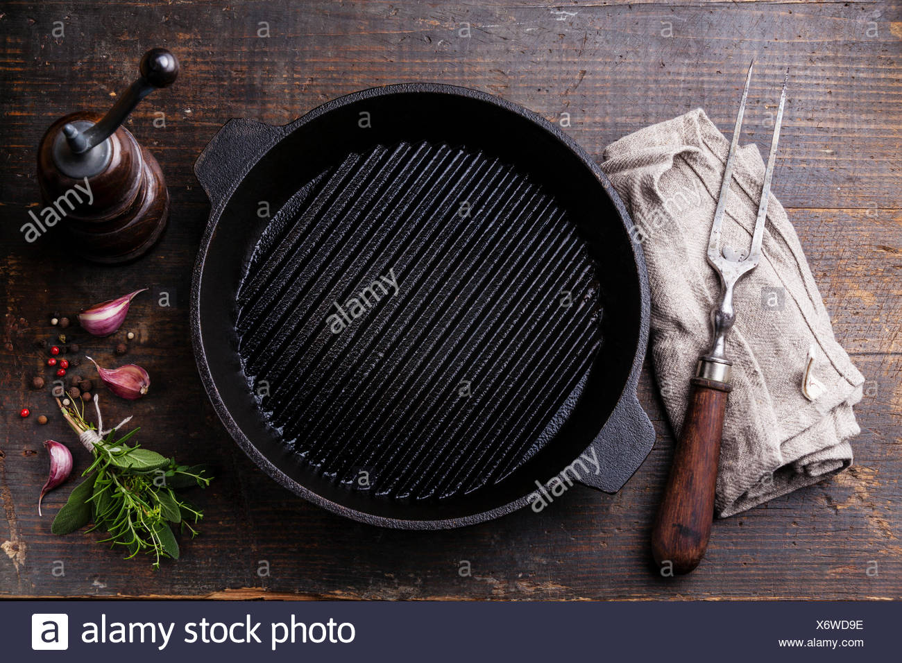 Black iron empty grill pan and meat fork on wooden texture background - Stock Image