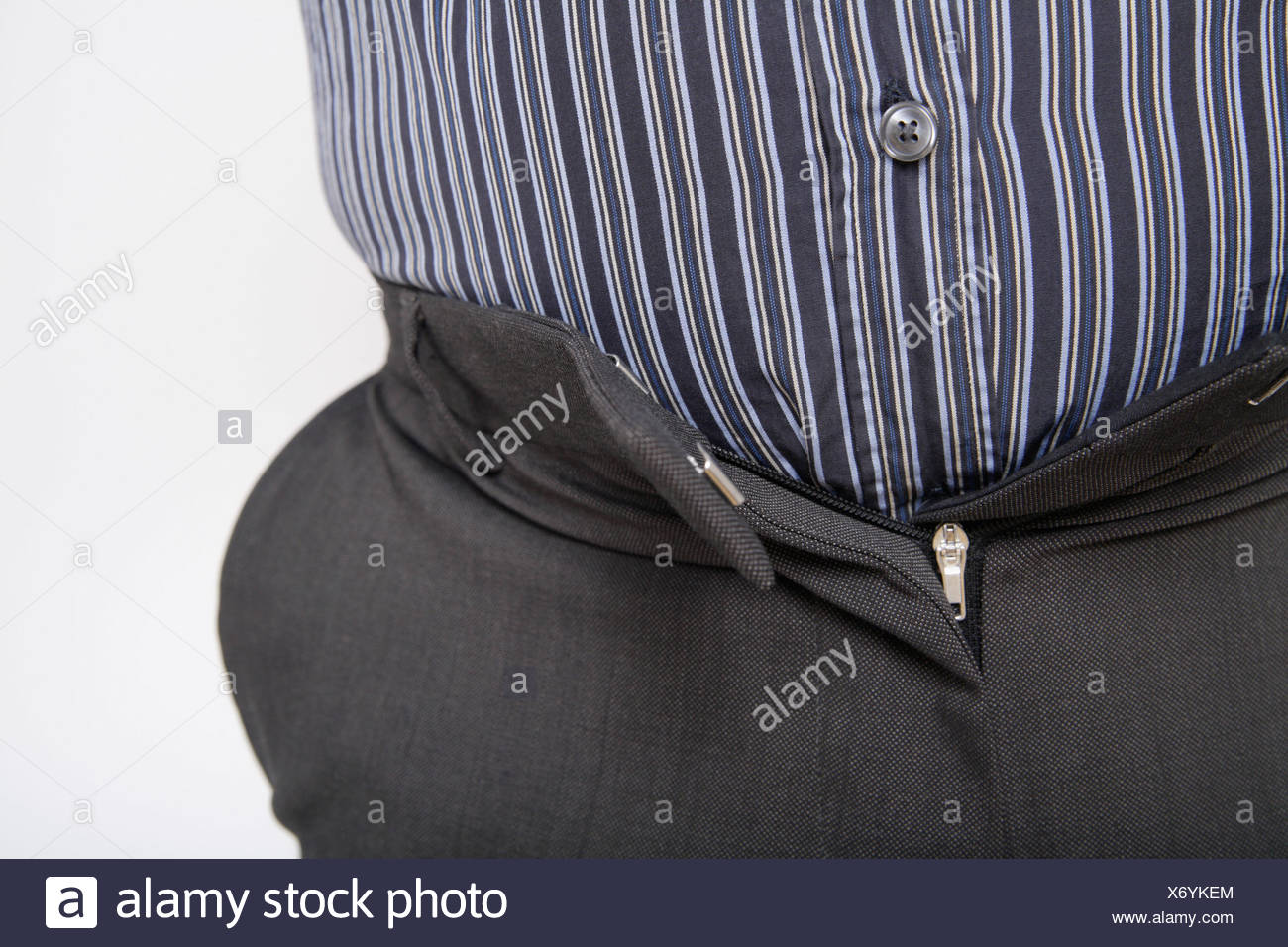 Close up of mature man with tight trousers against white background - Stock Image