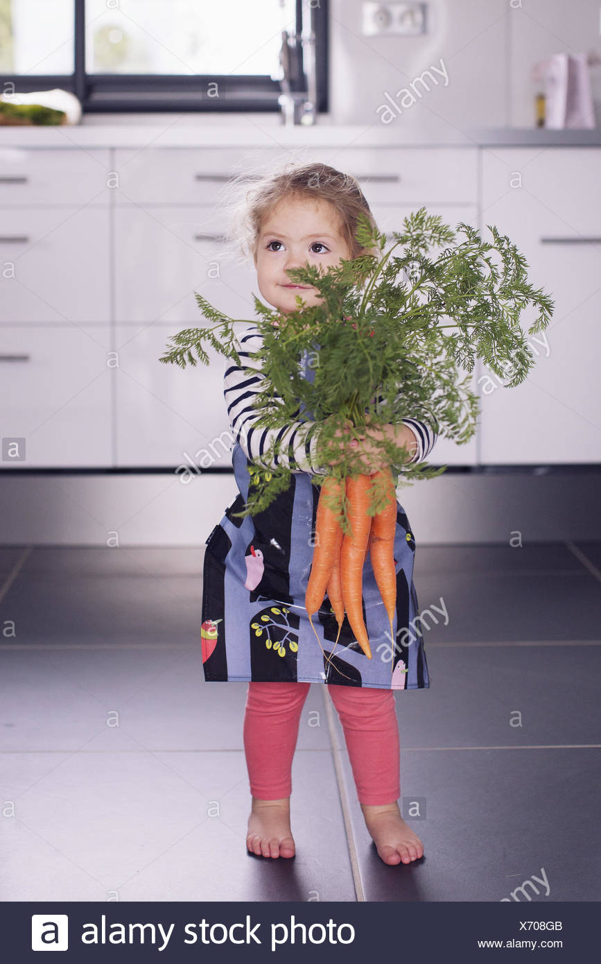 Little girl holding fresh carrots - Stock Image
