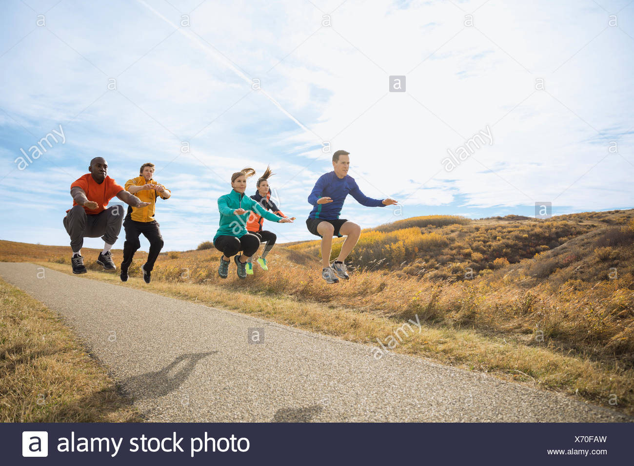Fitness group jumping on rural path - Stock Image