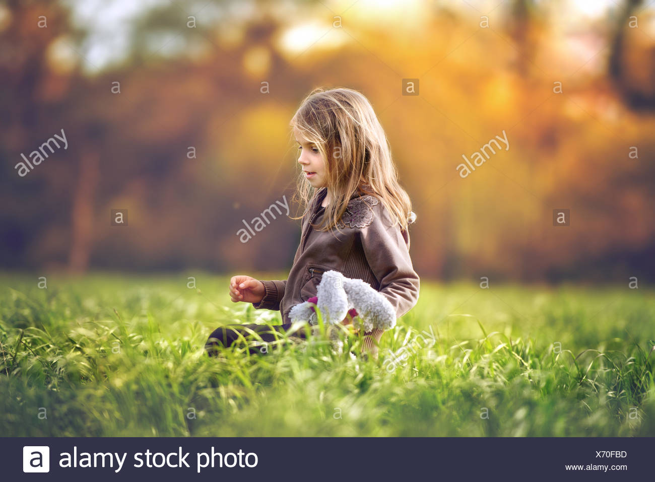 Girl sitting in a field holding a soft toy - Stock Image