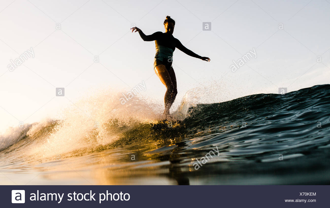 Women standing on surfboard, Malibu, California, USA - Stock Image