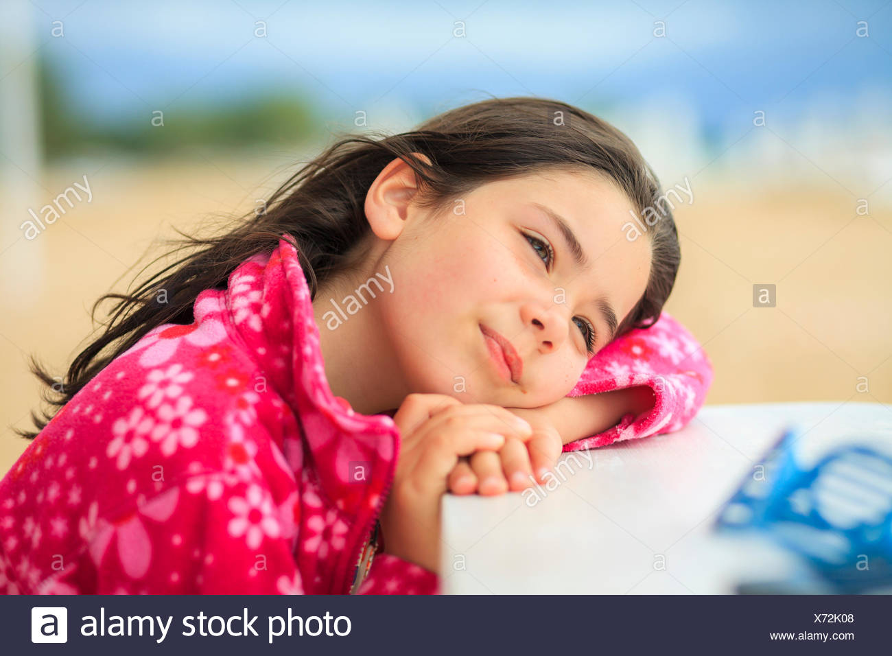 Girl resting her head on a table at the beach - Stock Image