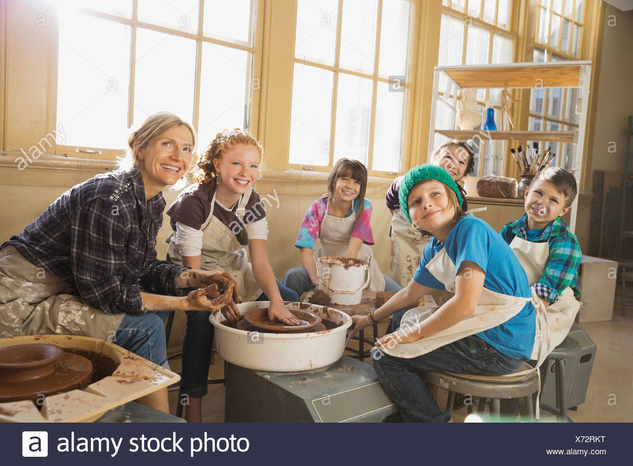 Teacher and students in pottery class - Stock Image