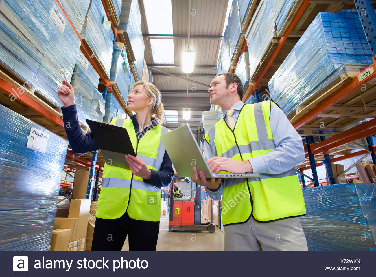 Warehouse manager and worker checking inventory with clipboard and laptop - Stock Image