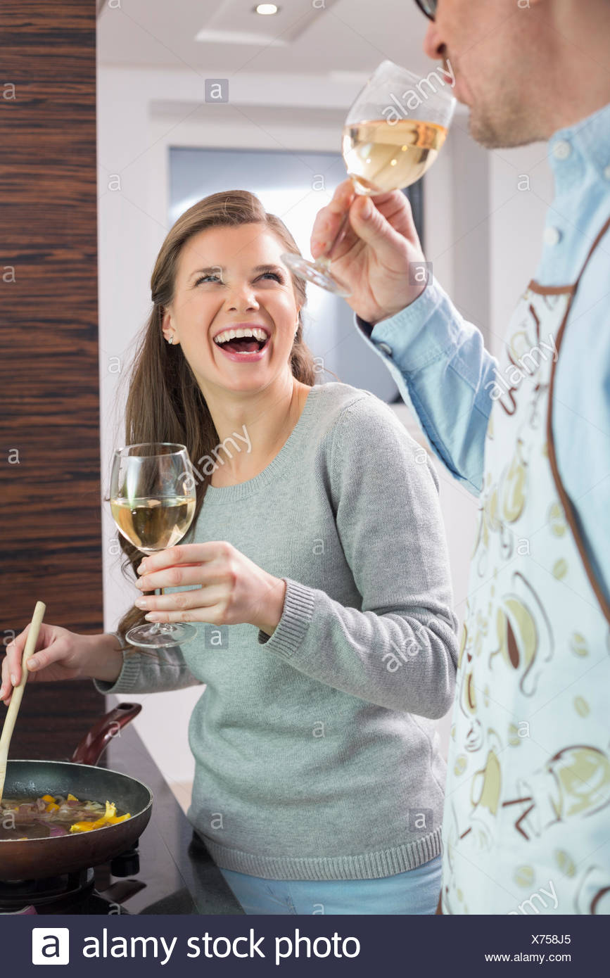 Cheerful couple having wine while cooking in kitchen - Stock Image